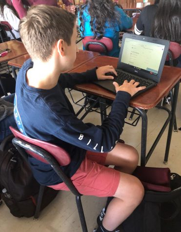 Austin Cincotta, freshman, starts of his Chromebook as class begins. He is one of over 500 freshmen who received the device.